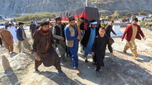 رجال أفغان يحملون نعش إحدى العاملات الإعلاميات الثلاث اللائي قُتلن برصاص مسلحين مجهولين في جلال آباد، أفغانستان في 3 مارس 2021.