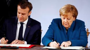 الرئيس الفرنسي إيمانويل ماكرون والمستشارة الألمانية أنغيلا ميركل خلال توقيع المعاهدة الجديدة بين البلدين
