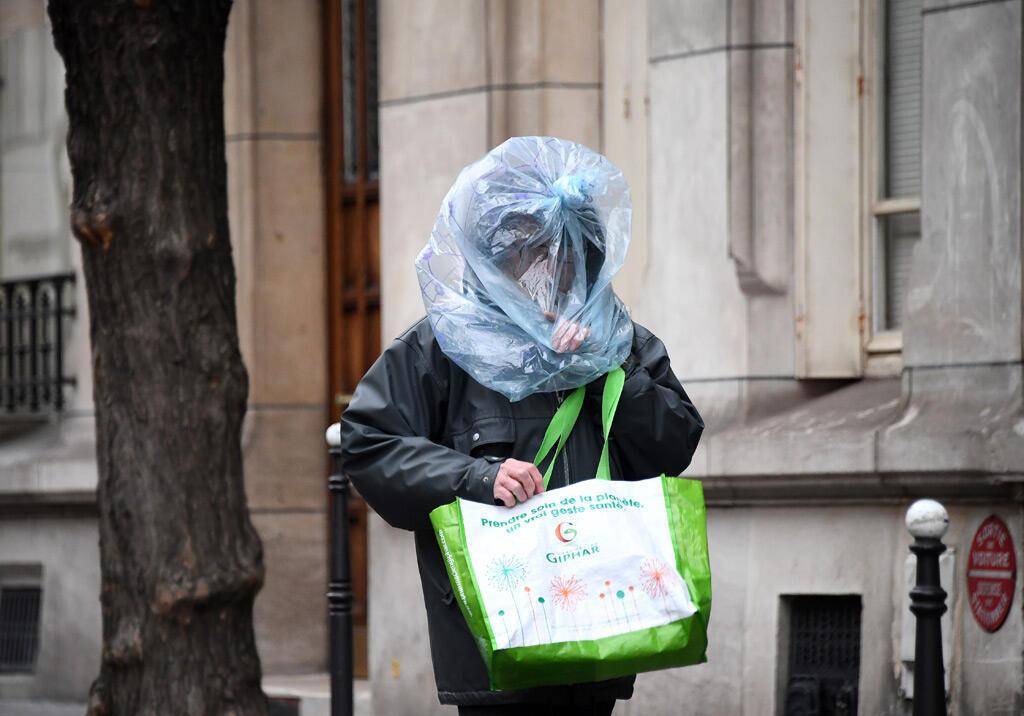 رجل يحمي وجهه بكيس بلاستيكي بينما كان يسير في الشارع في العاصمة باريس