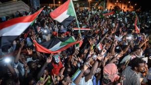 المتظاهرون السودانيون يرفعون إشارات النصر وأعلام الموجة وهم يتجمعون في اعتصام خارج المقر العسكري في الخرطوم في 19 مايو 2019