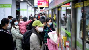 مسافرون صينيون ينتظرون القطار في ووهان يوم السبت 28-03-2020