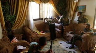 مقاتل من الجيش السوري الحر يطلق بندقية قنصه من منزل في حلب، سوريا -