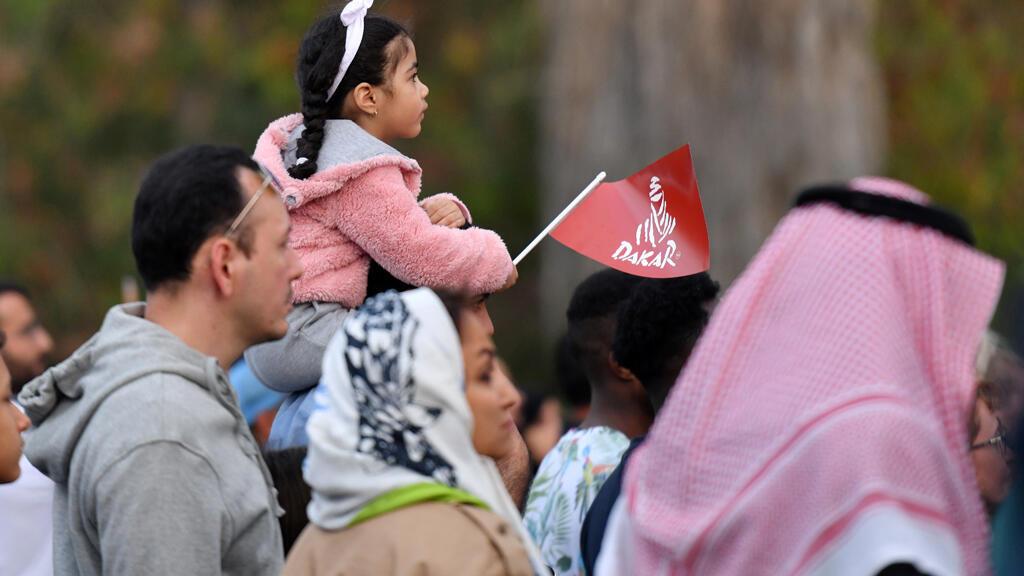 فتاة سعودية تحمل علم رالي داكار