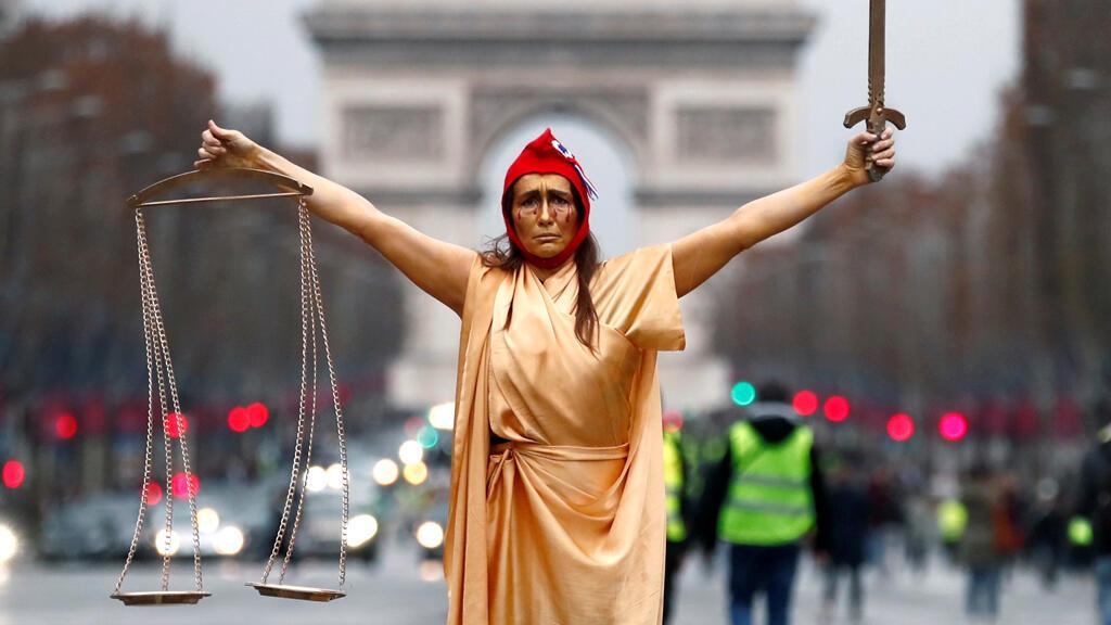 """إمرأة في زي """"ماريان""""، رمز الجمهورية الفرنسية، أثناء إحدى مظاهرات """"السترات الصفر"""" في باريس"""