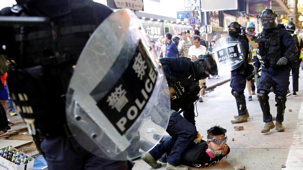 محتج مناهض للحكومة محتجز من قبل شرطة مكافحة الشغب خلال احتجاج في هونغ كونغ-