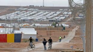 أطفال لاجئون سوريون يركبون دراجاتهم في مخيم الأزرق للاجئين