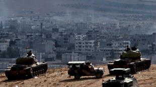 """دبابات تركية تطل على مدينة عين العرب/كوباني السورية خلال مواجهات الأكراد مع تنظيم """"داعش"""" في تشرين الأول 2014"""