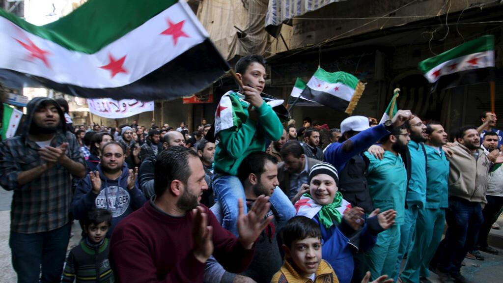 """متظاهرون يحملون """"علم"""" الثورة السورية في حي السكري في حلب"""