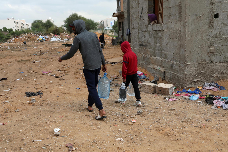 شخصان يحملان قوارير مياه في العاصمة الليبية طرابلس يوم 16 يناير كانون الثاني