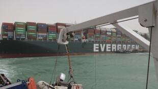 """زوارق مصرية تحاول مساعدة سفينة """"إم في إيفر غيفن"""" التايوانية التي تعرقل حركة الملاحة في قنال السويس يوم 25 مارس 2021"""