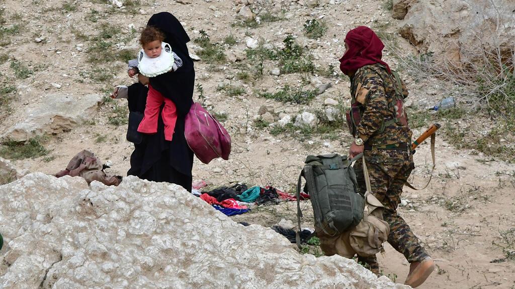 نساء وأطفال يتسلقون منحدراً  ويقال إنهم أعضاء في تنظيم الدولة الإسلامية (داعش) عند خروج قوات سوريا الديمقراطية من قرية باغوز في محافظة ديرالزور، سوريا