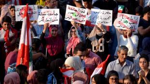 المتظاهرون يحملون لافتات خلال مظاهرة مناهضة للحكومة في طرابلس-