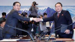 رئيس لجنة الوحدة في كوريا الشمالية ري سون جون (يمينا) يصافح وزير الوحدة الكوري الجنوبي تشو ميونج جيون بعد محادثات في قرية بانمونجوم الحدودية يوم الاثنين