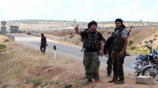 مقاتلون من فصائل إسلامية معارضة على الطريق بين أريحا (إدلب) واللاذقية أواخر أيار 2015