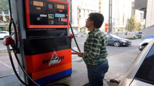 إيراني يراقب أسعار الوقود