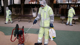 عمّال يستخدمون أدوات التعقيم في حديقة للأطفال، ضاحية سورين، باريس