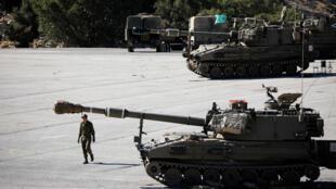 جندي إسرائيلي يسير بجوار وحدة مدفعية متحركة بالقرب من الجانب الإسرائيلي من الحدود مع سوريا في مرتفعات الجولان التي تحتلها إسرائيل-
