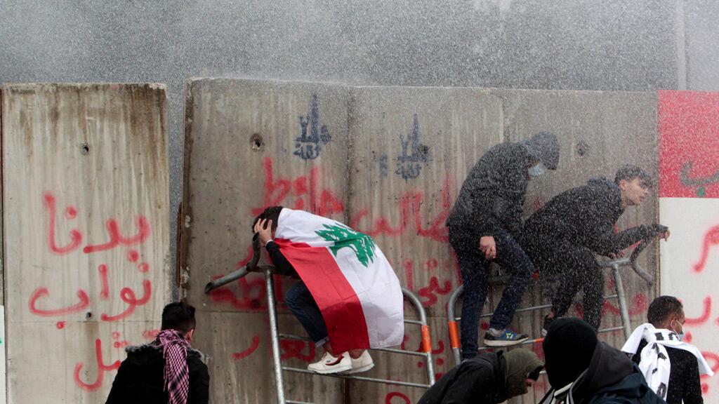 يتم رش المتظاهرين بمدفع المياه خلال مظاهرة تسعى لمنع النواب والمسؤولين الحكوميين من الوصول إلى البرلمان للتصويت على الثقة ، في بيروت