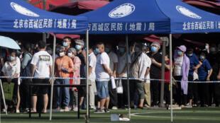 سكان يرتدون أقنعة أثناء انتظارهم للاختبار في مركز غوانجان الرياضي في بكين يوم 16 يونيو 2020