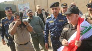 حيدر العبادي يحمل العلم العراقي بعد تحرير الموصل 09-07-2017