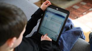 طفل يتلقى دروسه عبر الإنترنت بعدما أغلقت المدارس أبوابها، بريطانيا