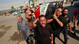 شبان غاضبون يحملون نعش إحد قتلى المظاهرات في العراق