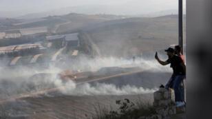 رجل يلتقط صورا للدخان الناجم عن قذائف إسرائيلية على قرية لبنانية بالقرب من الحدود مع إسرائيل