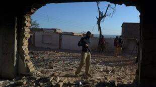 شرطي يقف أمام معبد هندوسي أحرقه حشد غاضب قبل يوم في قرية كرك على بعد 160 كلم جنوب شرق بيشاور