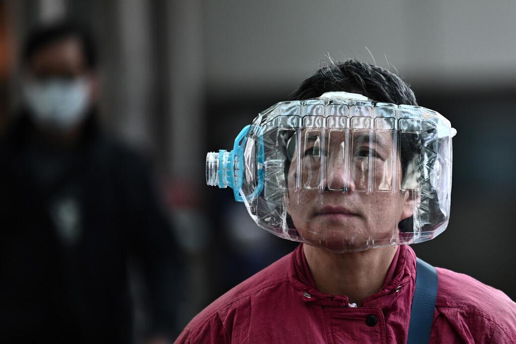 امرأة ترتدي زجاجة مياه بلاستيكية لتغطية وجهها وهي تمشي على جسر للمشاة في هونغ كونغ