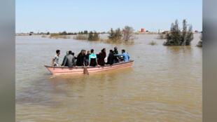 أشخاص يتنقلون على متن قارب بسبب فيضانات في إيران يوم 24 مارس آذار 2019