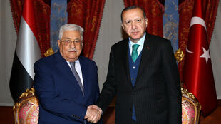 رئيس السلطة الفلسطينية محمود عباس يصافح الرئيس التركي رجب طيب أردوغان