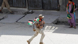 أحد أفراد قوات الأمن في محيط موقع انفجار في جلال أباد