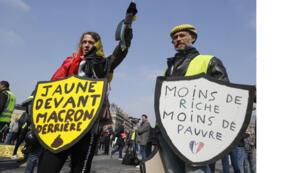 """متظاهرون من """"سترة الصفراء"""" يحملون لافتات مكتوب عليها """"عدد أقل من الأشخاص المتعافين ، وعدد أقل من الفقراء"""" و """"الأصفر أمام"""" ، ماكرون"""