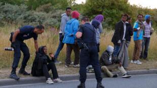 الشرطة تعترض طريق لاجئة تجلس على الأرض بالقرب من مدخل نفق المانش في منطقة كاليه الفرنسية