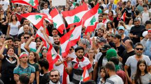 المتظاهرون يحملون الأعلام اللبنانية وهم يتجمعون خلال احتجاج على تدهور الوضع الاقتصادي في بيروت-