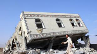 رجل يسير على أنقاض  مبنى منهار نتيجة غارة جوية في شمال غرب صعدة