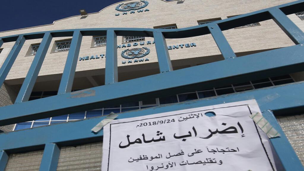 """لافتة باللغة العربية: """"إضراب شامل"""" على بوابة مغلقة لمركز صحي تديره وكالة الأمم المتحدة لإغاثة وتشغيل اللاجئين الفلسطينيين (الأونروا) خلال إضراب لجميع مؤسسات الأونروا في رفح"""