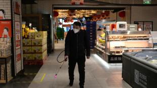 رش رذاذ في أحد المحلات الصينية للتطهير من فيروس كورونا