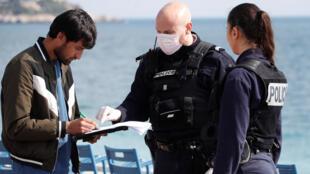 الشرطة الفرنسية تستجوب شخصا في ظل الإجراءات المفروضة لمحاربة فيروس كورونا، مدينة نيس، جنوب فرنسا