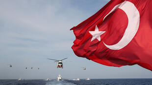 موجات العلم الوطني التركي بينما يشارك الجنود الأتراك في مناورة عسكرية للبحث والإنقاذ مع طائرات هليكوبتر وسفن بالقرب من ماغوسا ، قبرص ، في 12 يونيو2019  2019