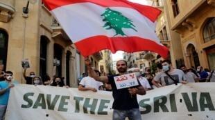 رجل يلوح بعلم وطني لبناني كبير أثناء مشاركته في احتجاج أمام مكاتب البنك الدولي