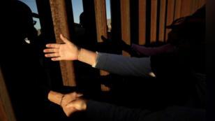 أناس يتصافحون على جانبي السياج الحدودي بين الولايات المتحدة والمكسيك