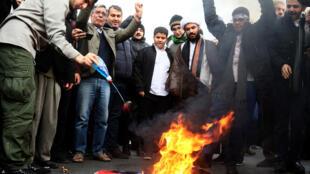 المحتجون الإيرانيون يحرقون العلم الأمريكي أثناء حضورهم مظاهرة في طهران-