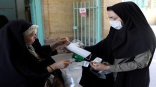 امرأة إيرانية توزع كمامات عند الدخول للمسجد