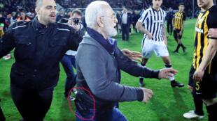 رئيس نادي باوك سالونيكي إيفان سافيدس يدخل أرض الملعب وهو مسلح احتجاجا على إلغاء الحكم هدفا لصالح فريقه