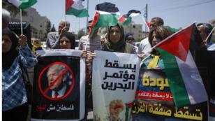 الفلسطينيون يحملون لافتات وشعارات يصرخون في مسيرة ضد مؤتمر السلام الإسرائيلي الفلسطيني الذي تقوده الولايات المتحدة في البحرين والمقرر عقده في الأسبوع المقبل ، في بيت لحم بالضفة الغربية المحتلة في 20 يونيو 2019