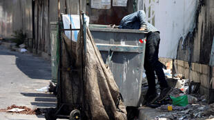 رجل يبحث في سلة مهملات في إحدى شوارع بيروت