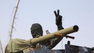 أحد عناصر قوات الأمن العراقية يرفع إشارة النصر
