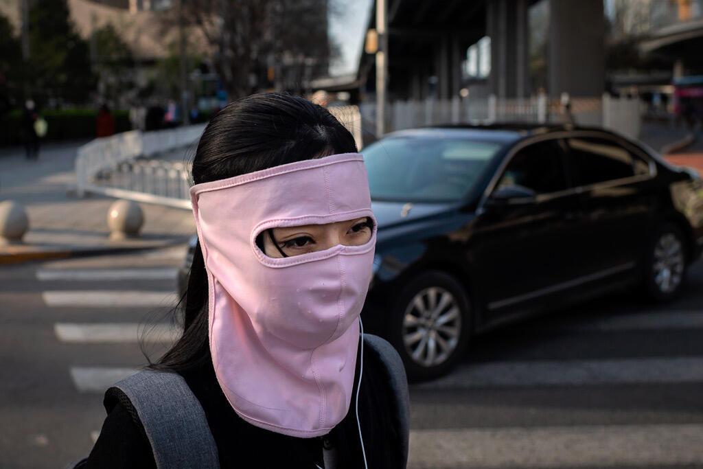 امرأة ترتدي قناع وجه من القماش بينما تمشي في بكين