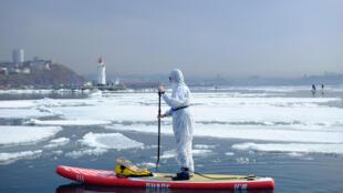 رجل يرتدي بدلة واقية لإظهار الدعم للأشخاص الذين يقاتلون ضد انتشار مرض فيروس كورونا  فوق الجليد